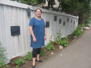 Stefanie Ivan in her poetry garden, a space she's created in her back alley in Griesbach. Photo by Eliza Barlow.